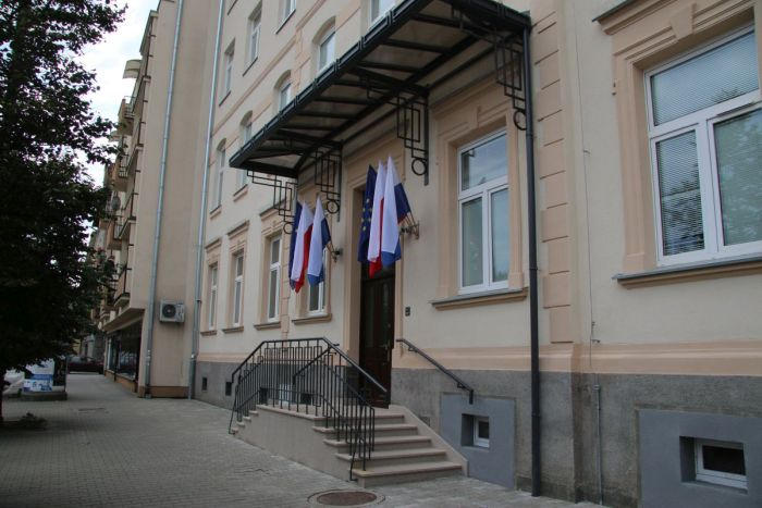 Entrance to the building in ul. Senatorska 9, visible stairs, canopy, 6 flags (2 Polish, 2 EU, 2 of Krakow).