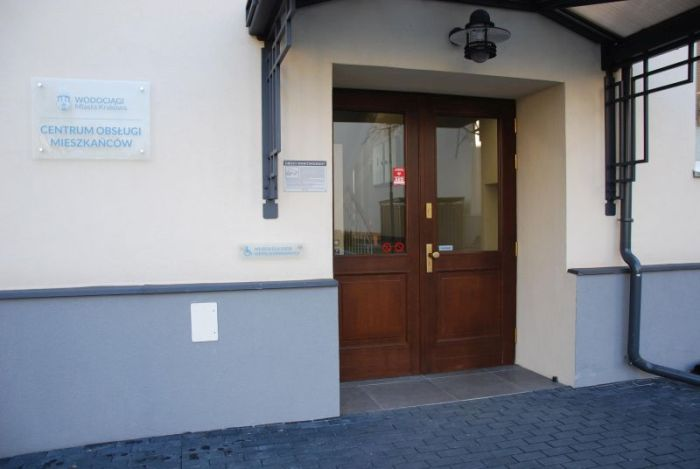 Entrance on the other side of the building: wide, glazed doors; board with the Kraków Water logo and the words Centrum Obsługi Mieszkańców.