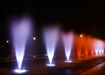 A fountain with gushing water, illuminated in white and blue.
