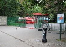 Pitnik in front of the gate leading to the park. On the side there is an information board