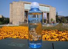 A water bottle with tap water. Yellow flowers and the National Museum in the background.