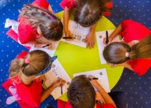 Children at the round table are solving crosswords.