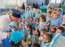 Grandpa Tadek distributes cups of water to children dressed as water droplets.