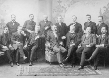 Group photo of employees sitting on chairs in elegant costumes. Black and white.
