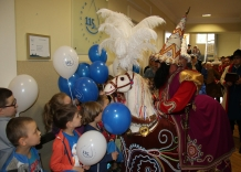 Lajkonik on horseback surrounded by children with blue and white balloons.