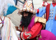 Lajkonik in a colorful disguise on horseback. In the background, people are standing on the stairs.