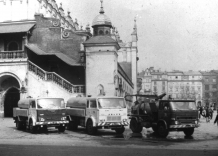 Vintage photo of three specialized cars on the Main Market Square. The cloth hall is visible in the background.