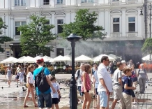 People cool themselves down with a water curtain placed in the Main Market Square.
